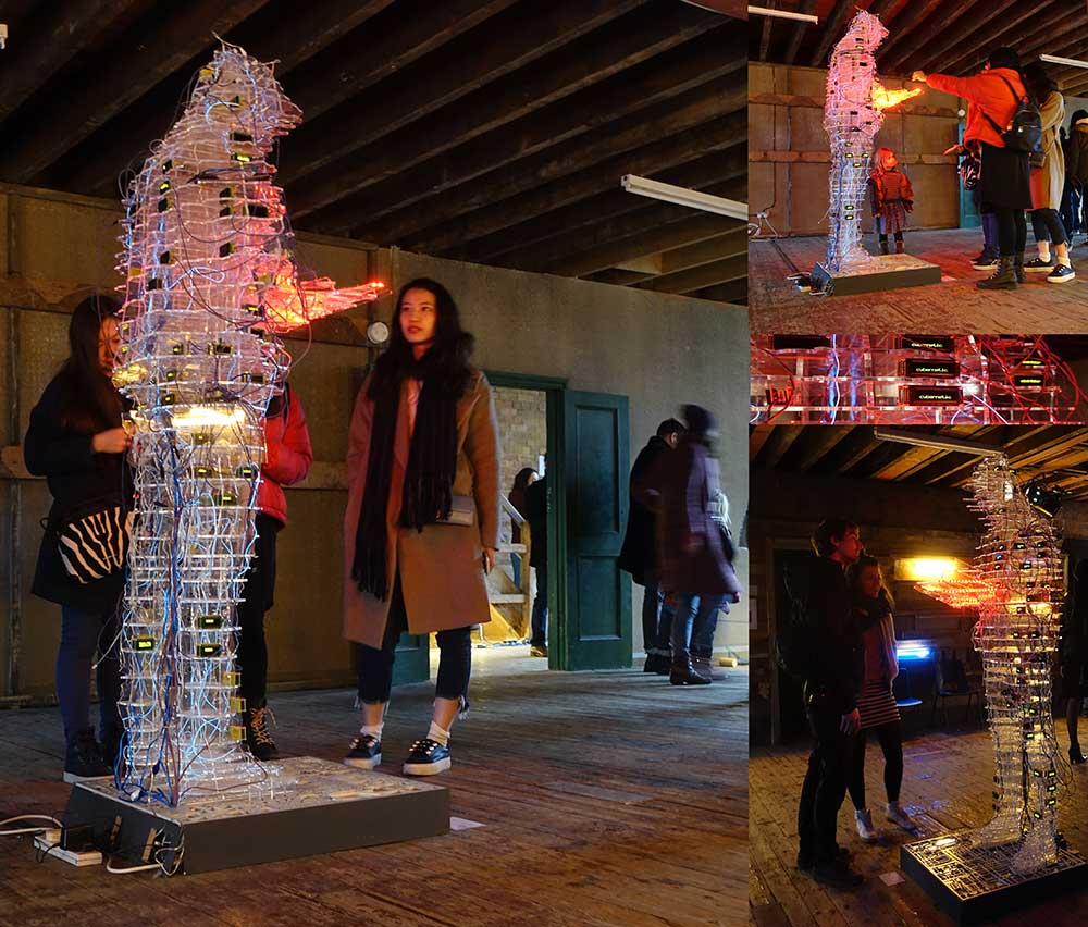 The Reader is large six foot data visualization sculpture of the artist Stanza wearing a hoodie reading a book